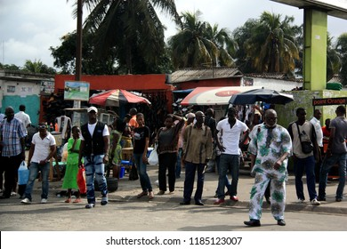 Abidjan, Cote d'Ivoire - October 1st, 2012: African people waiting for the bus in front of some market stalls and mini markets