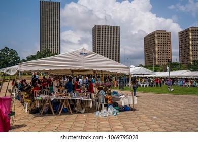 ABIDJAN, CÔTE D'IVOIRE - October 21, 2017: Local people selling religious items during an organization near St. Paul's Cathedral, with buildings in the background.