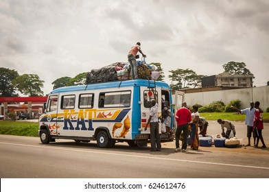 ABIDJAN, IVORY COAST, AFRICA. July 2, 2013. African passengers boarding the local shuttle minibus. Usually African buses are overcrowded and the ride is not safe. African bus travel concept.