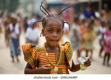 Abidjan, Ivory Coast- February 13, 2018: Portrait of an unidentified girl in a dress made of loincloth and pigtails in animal horns, wearing a necklace and looking at the camera