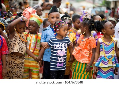 Abidjan, Ivory Coast - February 13, 2018: Unidentified children from a nursery school disguised in several outfits of the country parade in a street of the capital in a group.