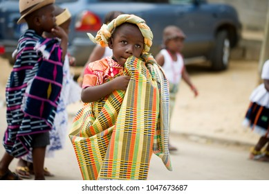 Abidjan, Ivory Coast - February 13, 2018: Little boy walking in the street dressed in a loincloth and a crown made in a piece of loincloth with behind him some friends.