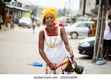 abidjan, ivory coast - February 13, 2018: Young Ivorian woman in white camisole, her head tied with a piece of yellow loincloth, taps a drum that she holds in her hand in the street.