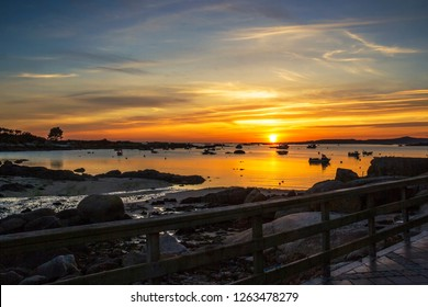 Abilleira beach in Arousa Island at golden and cloudy sunset with fishing boats anchored on the estuary