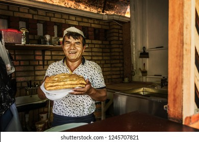 ABKHAZIA, GEORGIA - CIRCA JUNE 2018: A male cook, a migrant worker from Central Asia, bakes delicious chebureks and hospitably shows his product.