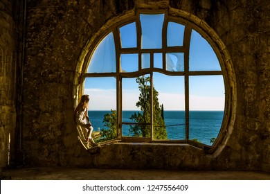 ABKHAZIA, GEORGIA - CIRCA JUNE 2018: The girl looks curiously out into the historic pomegranate window of the abandoned castle of the Prince of Oldenburg in Gagra