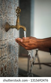 Ablution flow before perform a prayer in a mosque by using classic pipe. Image may soft and contains grain due to photo effect and vintage lens quality.