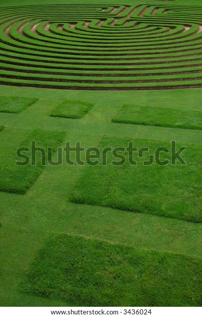 Ably trimmed  lawn forming a 3d maze and figures in a formal English garden