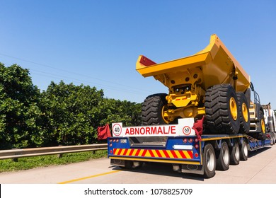 Abnormal vehicle haulage low bed trailer delivery of new large heavy industrial mining construction truck on road highway.