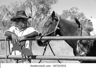 Aboriginal cattleman or stockman resting with horses having a cigarette in outback Australia between mustering cattle