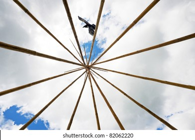 An aboriginal tee pee frame as a raven passes over head.  The raven is a symbolic bird in native folklore and traditional story telling.  Wide angle.