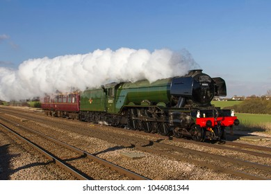 ABOTTS RIPTON, CAMBRIDGESHIRE, UK – FEBRUARY 24, 2016: Steam locomotive LNER Class A3 Pacific No. 60103 'Flying Scotsman', heads to London along the ECML.  Electrification digitally removed.
