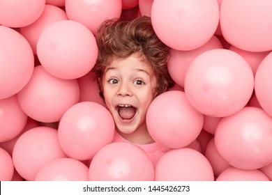 From above adorable boy with curly hair screaming and having fun while playing in heap of pink balloons