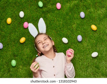 From above adorable girl with bunny ears holding colored Easter eggs and laughing while lying on green grass