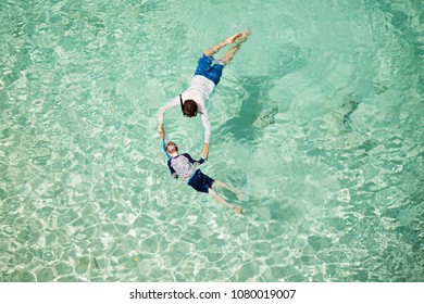 above aerial view of family of two, father and son, enjoying snorkeling in beautiful turquoise lagoon at anguilla island, caribbean, active family vacation concept
