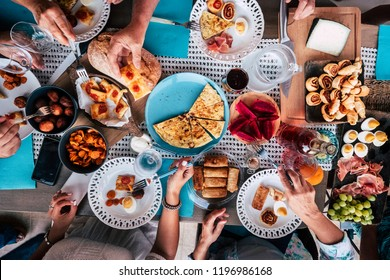 Above aerial view of group of friends having fun eating together at lunch or dinner with a table full of different and colorful food and technology mobile phone. mix of hands of caucasian people