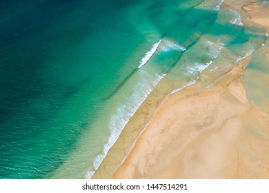 Above aerial view of scenic waves of turquoise water at yellow sand beach