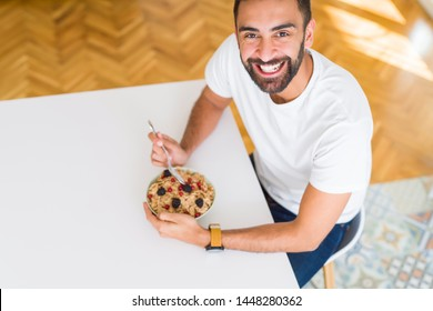 Above angle of handsome man eating healthy cereals for breakfast in the morning