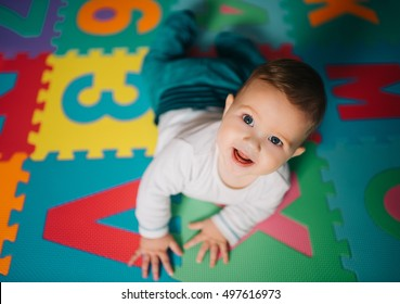 Above angle shot of adorable Baby boy lying on child friendly floor puzzle mats looking up