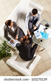 Above angle of successful associates making agreement at meeting