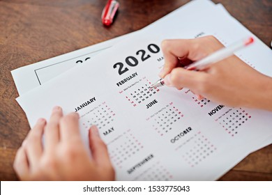From above anonymous freelancer circling date on year 2020 calendar while working at desk in home office