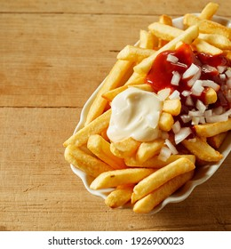 From above of appetizing golden fried potatoes with mayo and tomato sauce served with fresh chopped onion in plate placed on wooden table