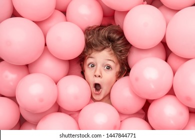 From above astonished little boy looking away while having fun under heap of pink balloons during party