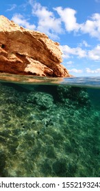 Above and below underwater photo of tropical exotic island arch cave with emerald sea and deep blue sky