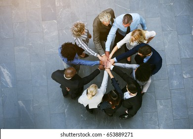 From above black and white coworkers having teambuilding in hall of office standing with hands stacked.