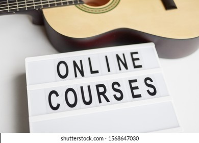 From above board with Online courses writing placed near acoustic guitar during advertisement campaign against white background
