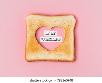 From above bread with heart cut and Be my valentine words on pink background.