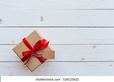 Above brown gift box and red ribbon with tag on wooden board background with space.