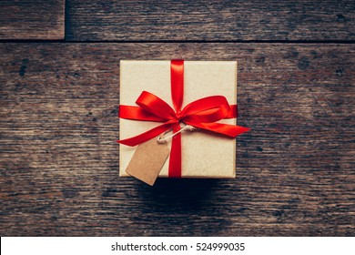 Above brown gift box and red ribbon with tag on wood background with space.