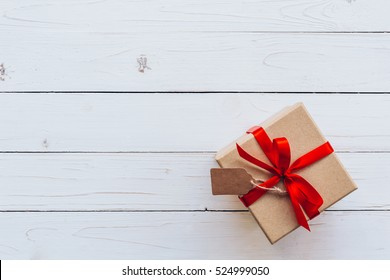 Above brown gift box and red ribbon with tag on white wooden board background with space for text.