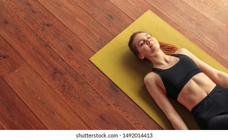 From above calm fit woman relaxing and breathing while lying at corpse pose on mat