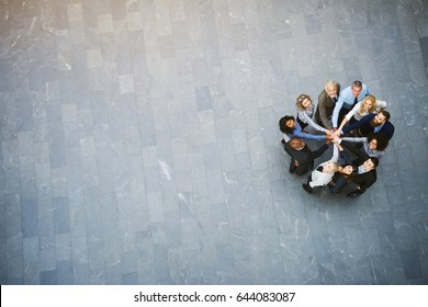 From above cheerful black and white office workers standing in hall with hands stacked during teambuilding.