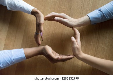 Above close up view four human hands businesswomen and businessman making a circle on wooden background, teammates join palms in shape of circle, protecting and showing care of their business concept