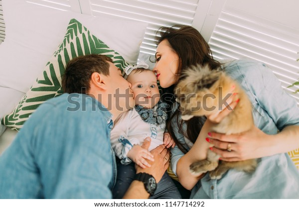 The above close-up portrait of the parents kissing their child and holding the rabbit while lying on the bed.