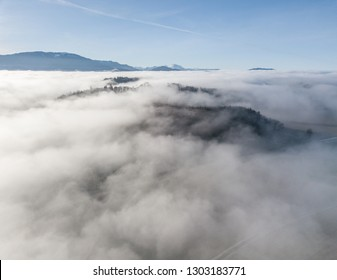 Above the clouds. Aerial view of of clouds and fog over rural area in Switzerland. Beautiful sunlight on cold winter morning with misty conditions.