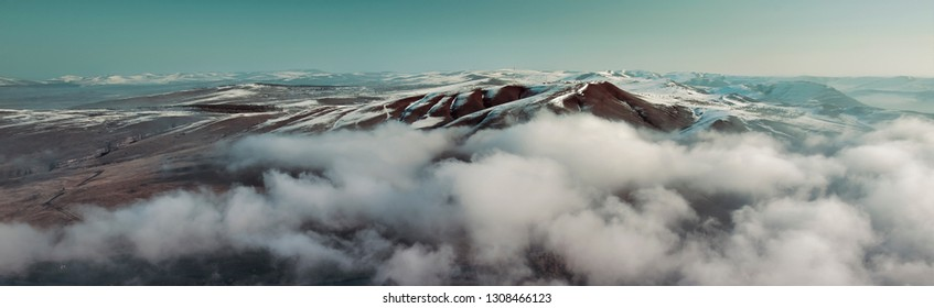 Above the clouds. Winter landscape snow mountain high angle view from airplane. Aerial view of siberian mountain landscape with peaks covered by snow and clouds.