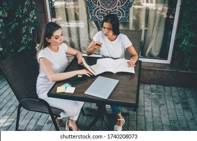 From above of concentrated female freelancers in white outfits sitting at table while working with documents and devises at cafe terrace