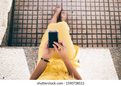 From above crop businesswoman in elegant yellow dress and golden sandals interacting with smartphone while sitting alone on stone bench on street in city