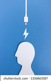 From above cutout recharge cable and energy icon near silhouette of human head on blue background