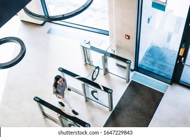 From above of dark haired female in casual shirt and white trousers passing trough turnstile in spacious bright corridor of modern building
