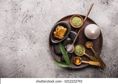 From above different items for spa procedures on wooden tray on rough background.