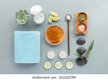 From above different products and equipment for spa procedure on gray background.
