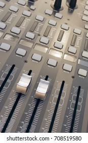 From above different sliders and buttons on professional sound board.