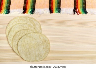 From above fresh tasty traditional tortillas placed on wooden table.