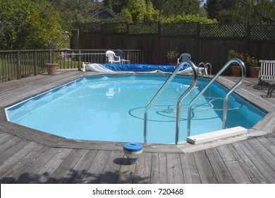 """An above ground """"Doughboy"""" swimming pool surrounded by decking."""