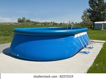An above ground pool sets on a concrete pad in the backyard on a sunny summer day.